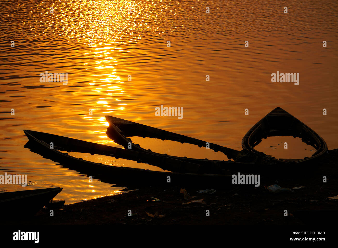 Tree wooden boats fill with water at the sun set - Stock Image