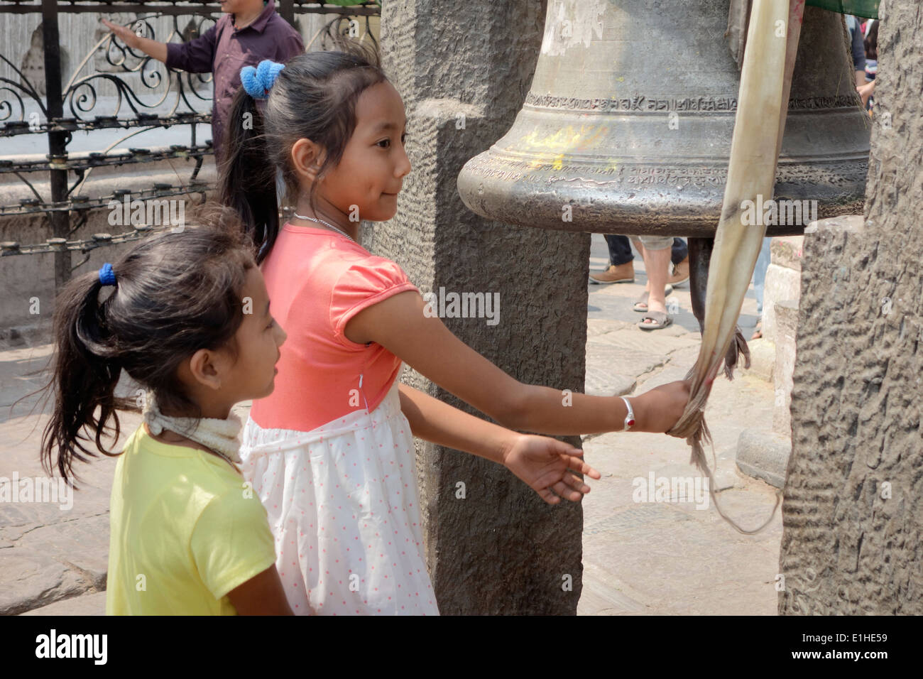 two young girls are ringing big bell at  Swayambhunath temple,innocence,cute,unusual,rare,mystery, - Stock Image