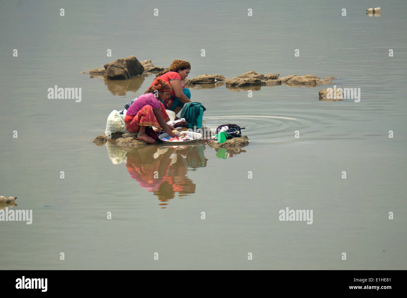 Two women are doing laundry in the lake - Stock Image
