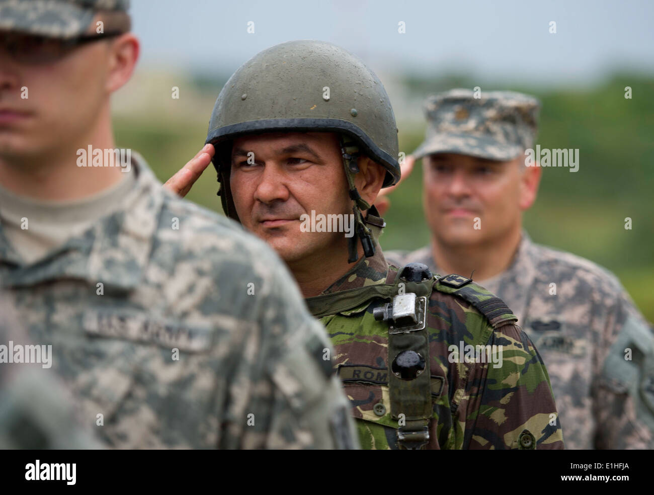 A Ukrainian Ground Forces soldier with the 80th Airborne Regiment salutes with U.S. Soldiers assigned to the Joint Regional Det - Stock Image