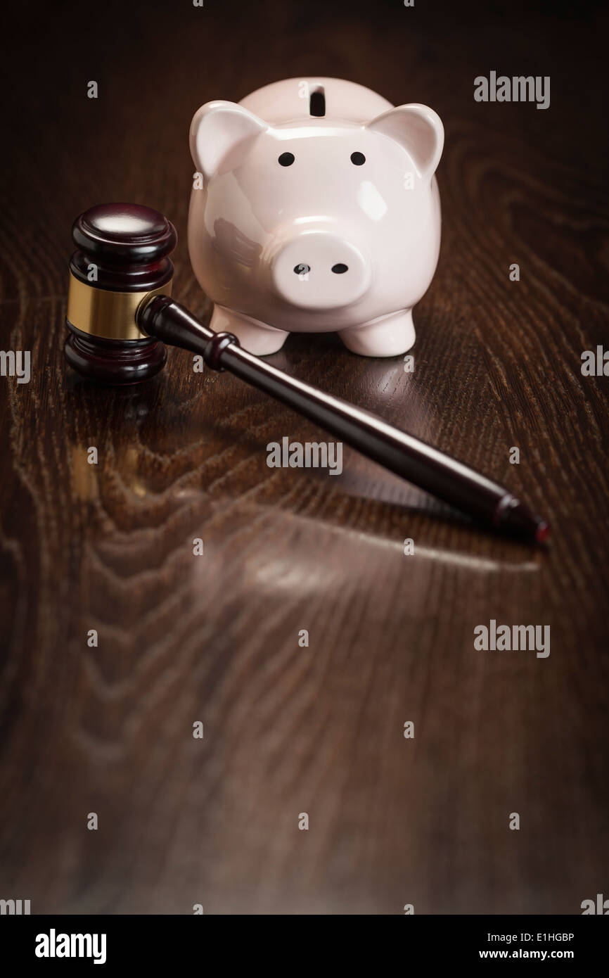 Gavel and Piggy Bank on Wooden Table. - Stock Image