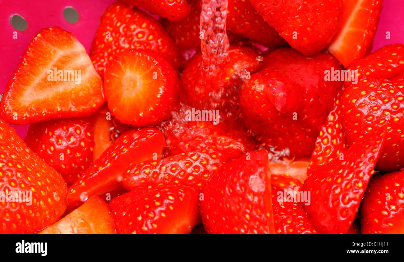 A close up of strawberries being washed - Stock Image