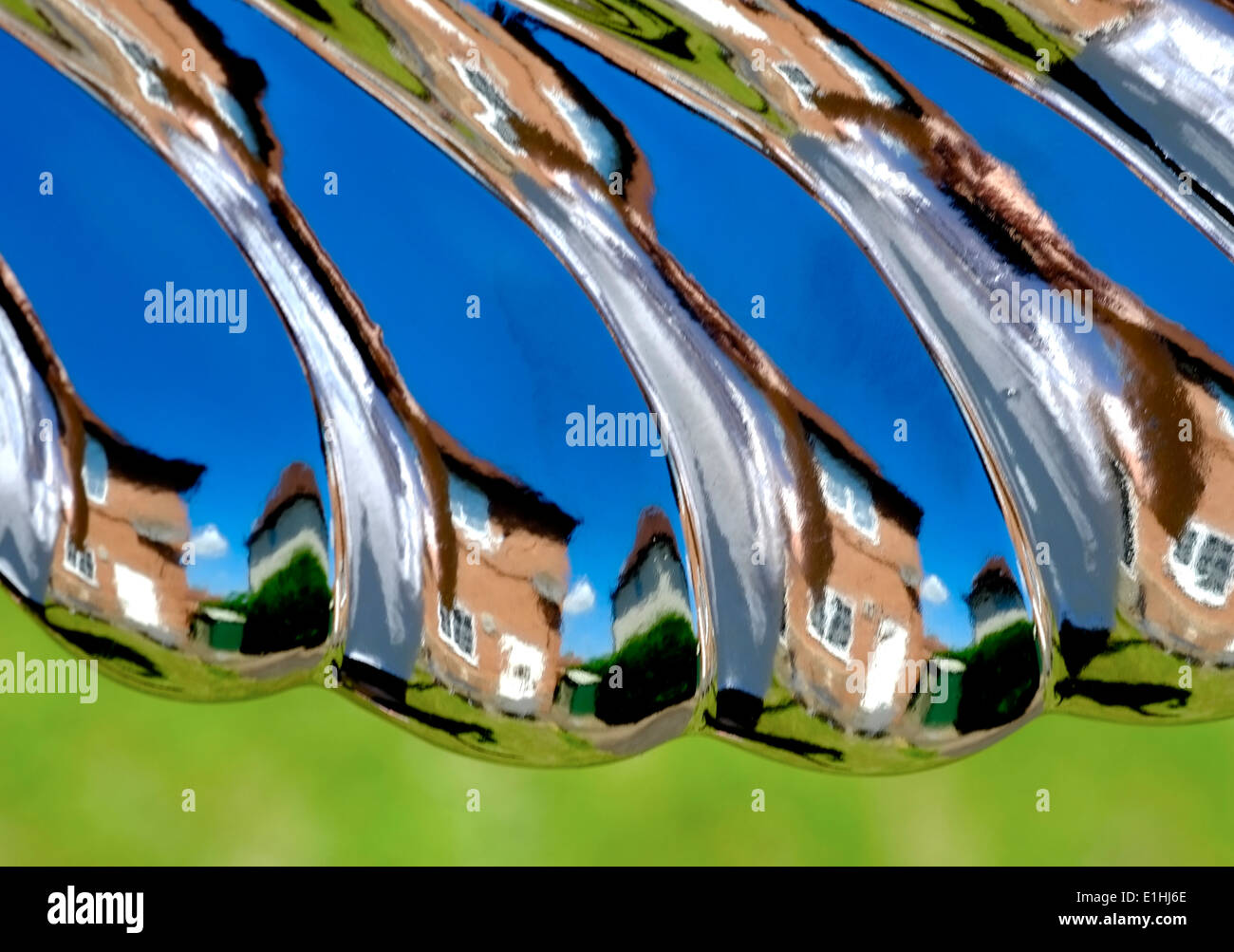 A warped image of a house and garden England uk. Reflection from a garden ornament - Stock Image