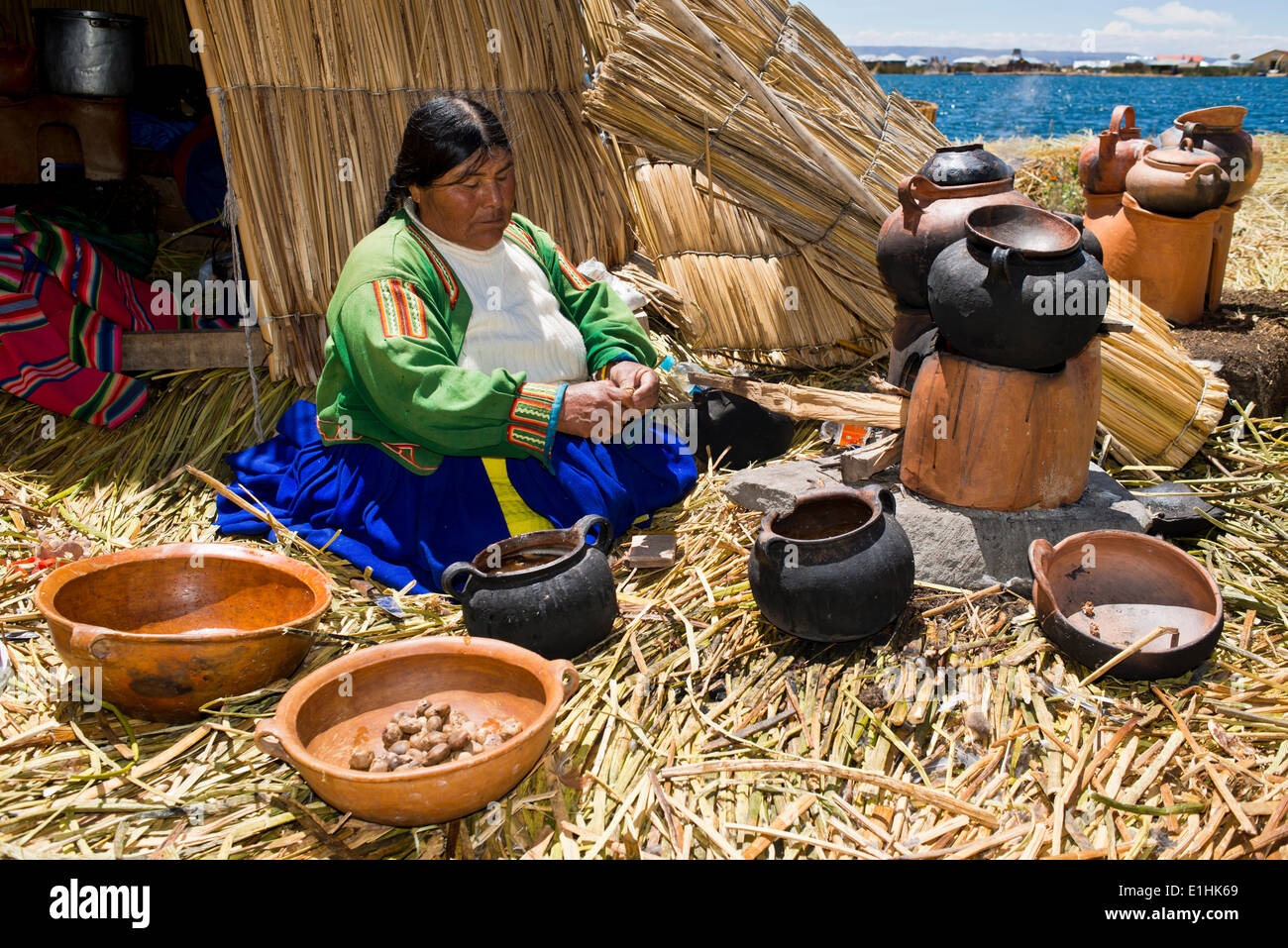 An elderly woman of the Uro Indians wearing typical attire, sitting in front of a reed hut with clay bowls and pots while - Stock Image