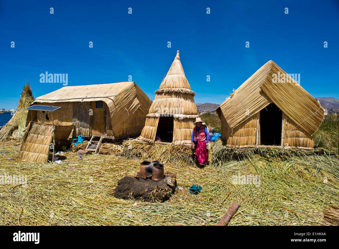 Woman of the Uro Indians in front of typical reed huts, traditional clay oven in the foreground, floating islands made of totora - Stock Image