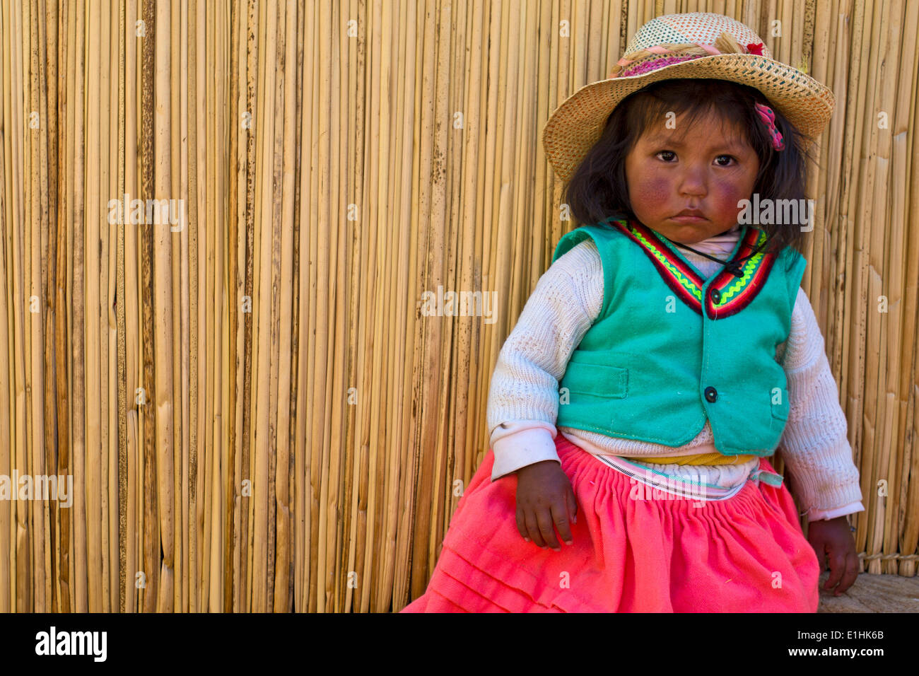 Young girl of the Uro Indians, about 6 years old, wearing traditional dress in front of a reed hut, floating islands made of - Stock Image