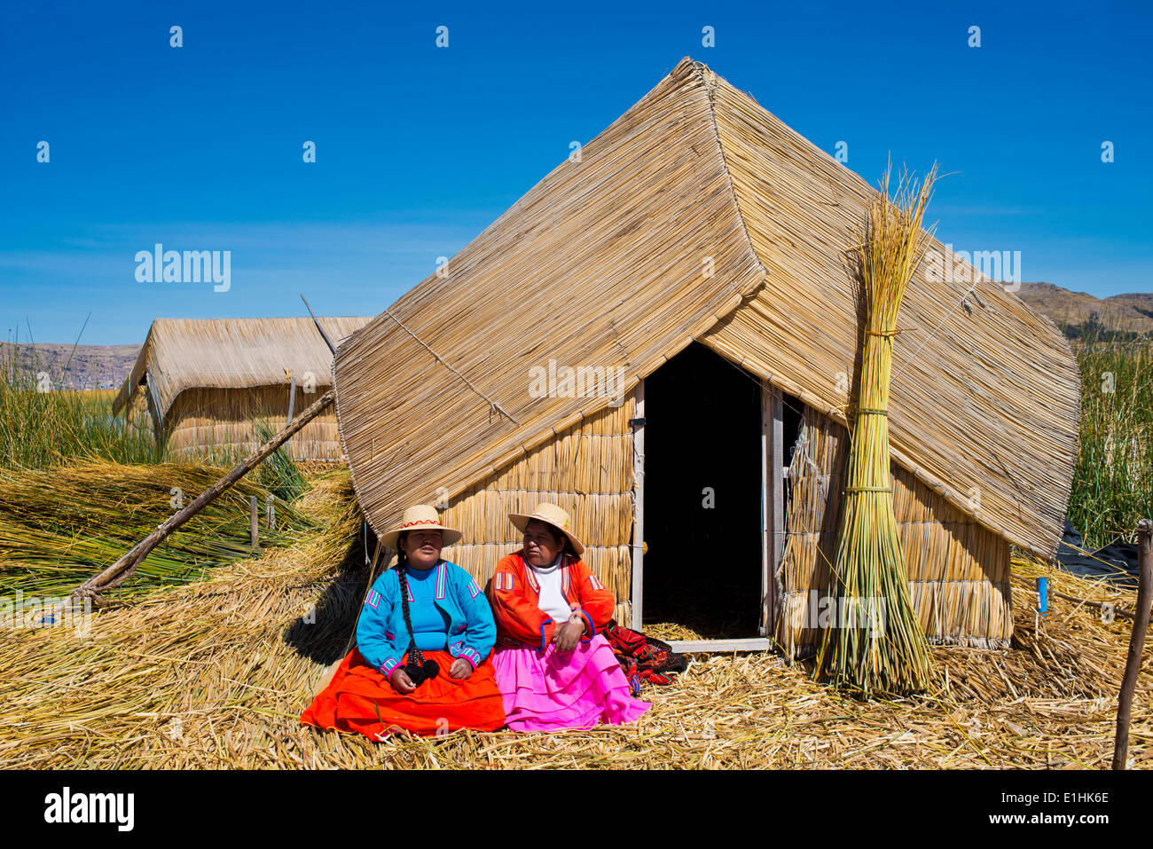 Two women of the Uro Indians wearing traditional dress sitting in front of a reed hut, floating islands made of - Stock Image