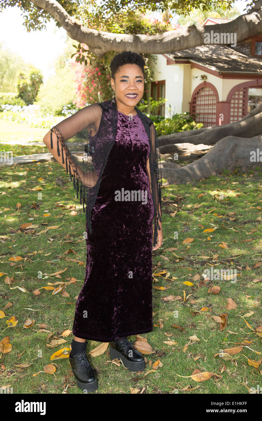 Outdoor portrait of a Black young woman in a purple velvet gown ...