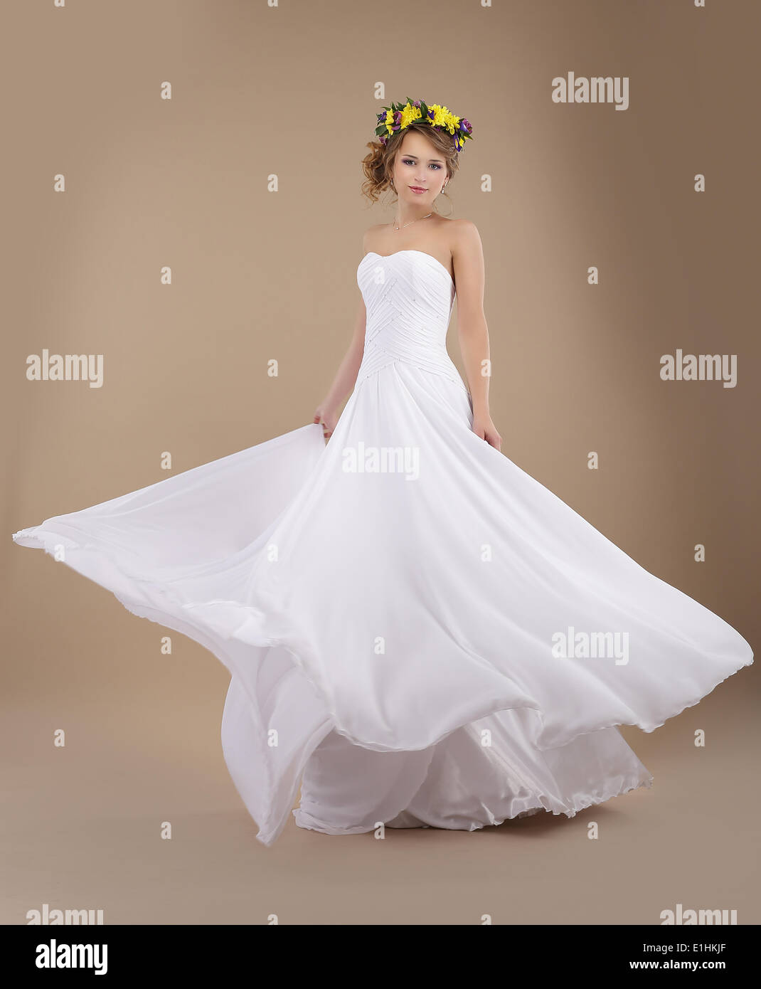 Beautiful Fiancee with Vernal Wreath of Flowers in Flying Wedding Dress - Stock Image