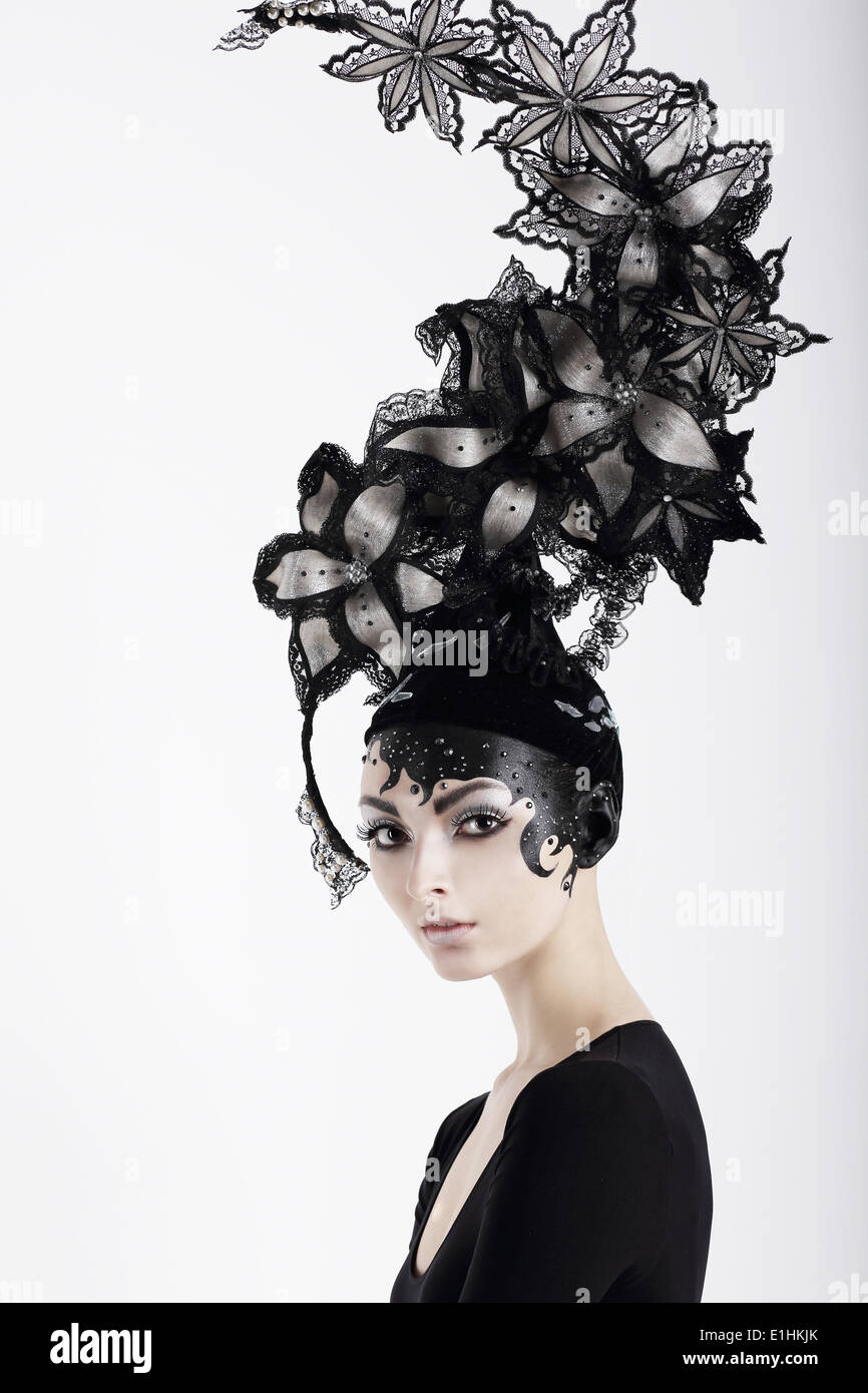 Stylish Eccentric Woman with Fanciful Make-up and Outlandish Hat - Stock Image