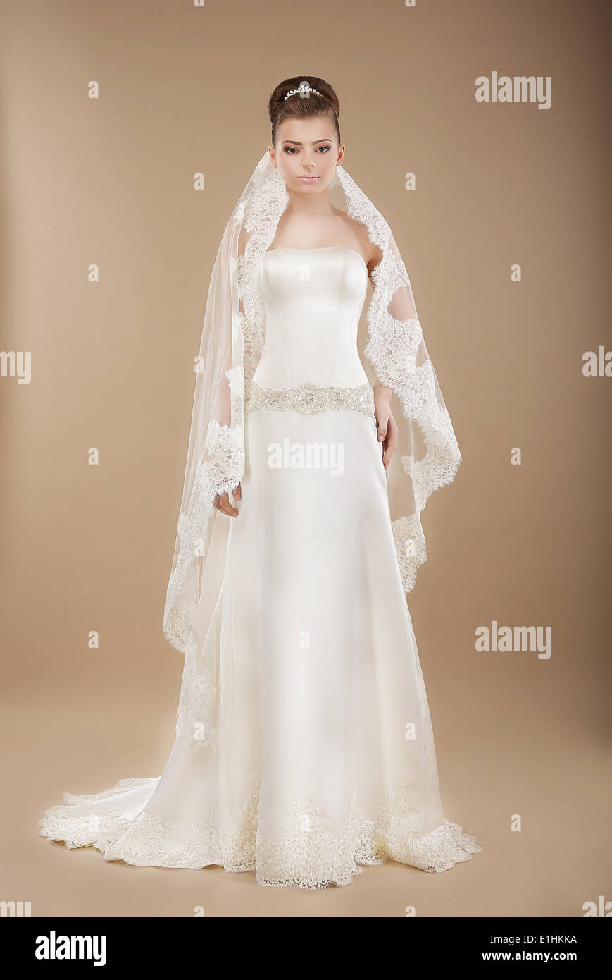 Young Bride in Wedding Lacy Dress over Brown Background - Stock Image