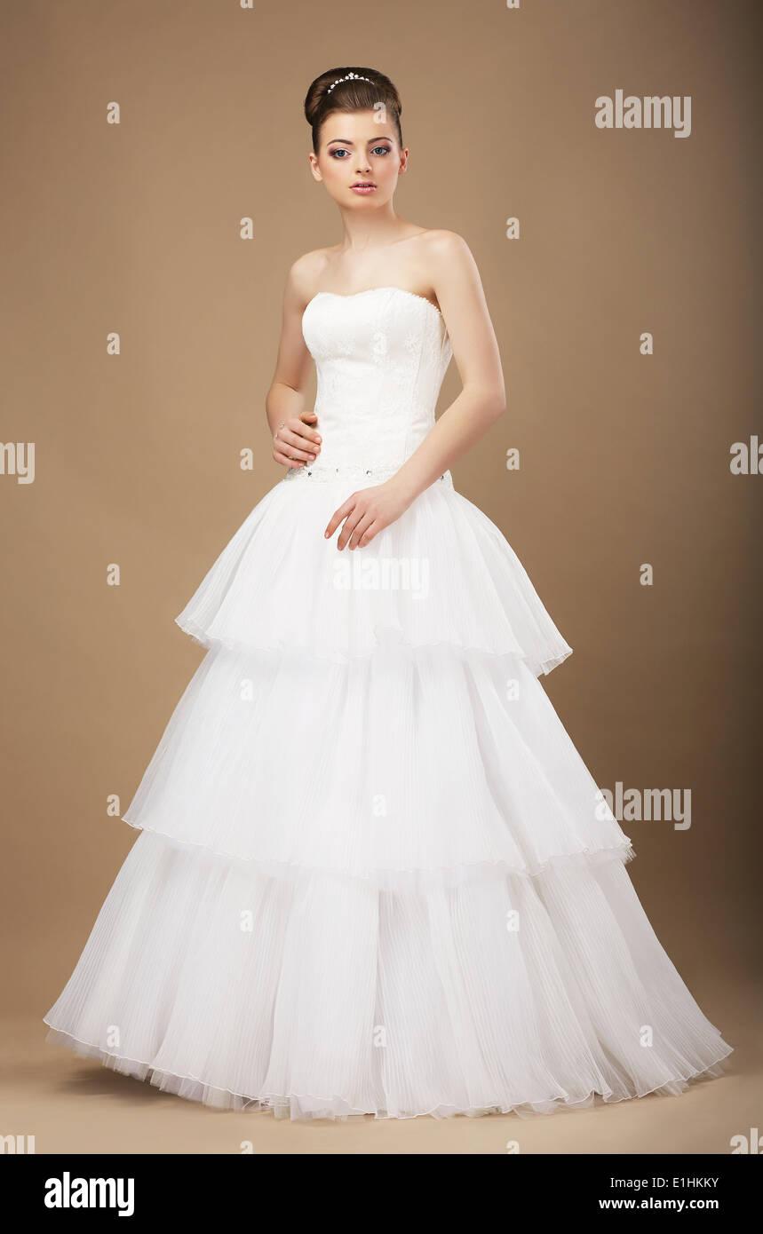 Caucasian Woman in White Long Dress Posing in Studio - Stock Image