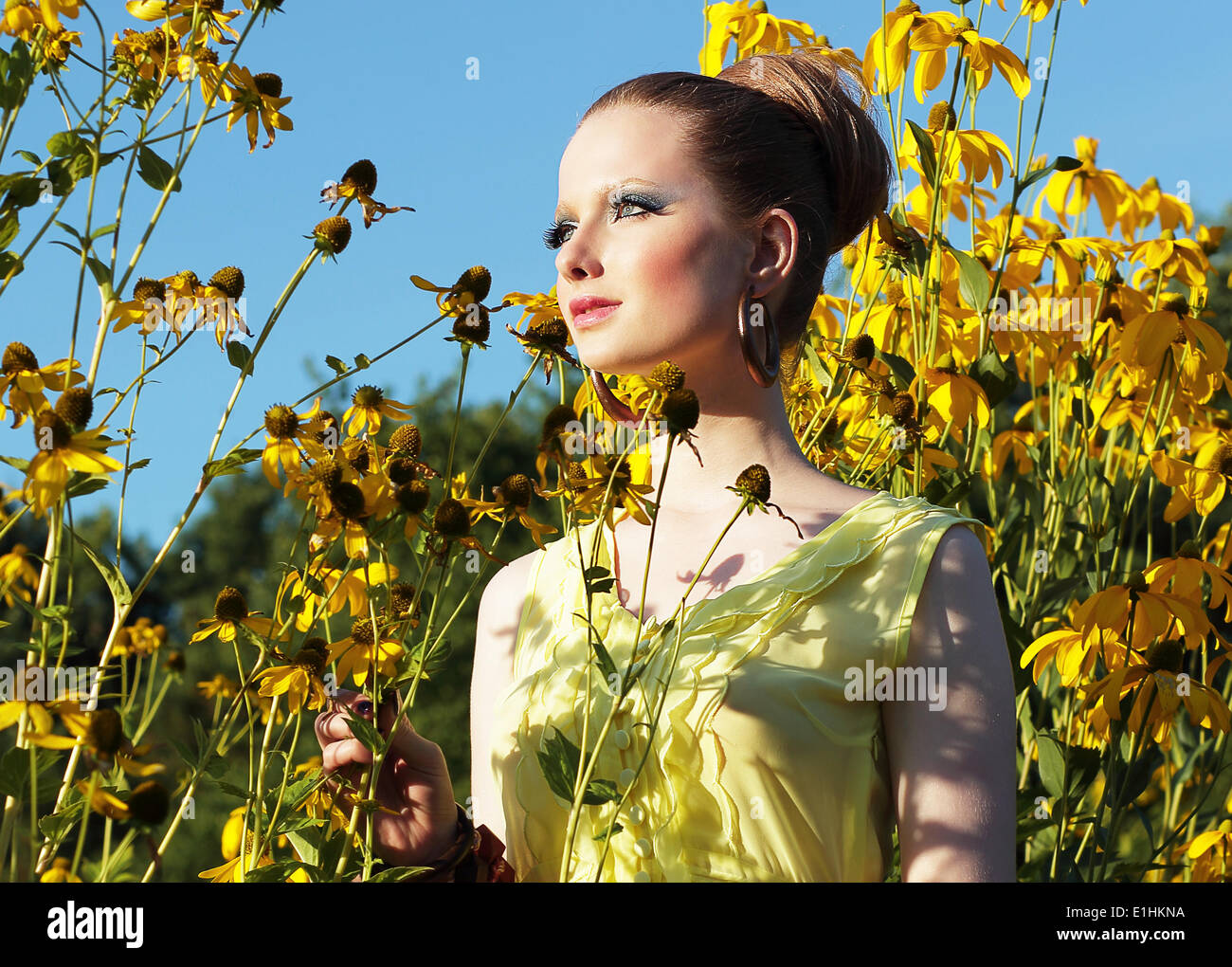 Summertime. Young Female in Meadow among Blooming Yellow Flowers - Stock Image