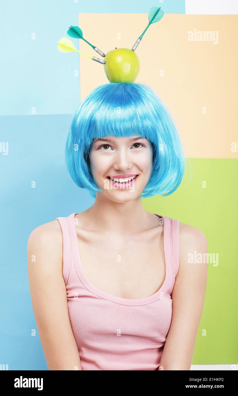 Precision. Amusing Woman in Blue Wig, Green Apple and Darts - Stock Image