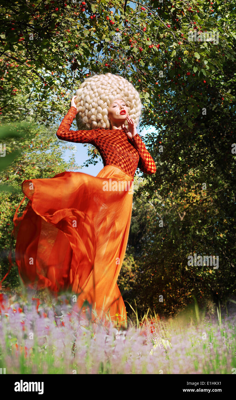 Extravagant Woman in Fluttering Dress and Luxurious Wig with False Hairs - Stock Image