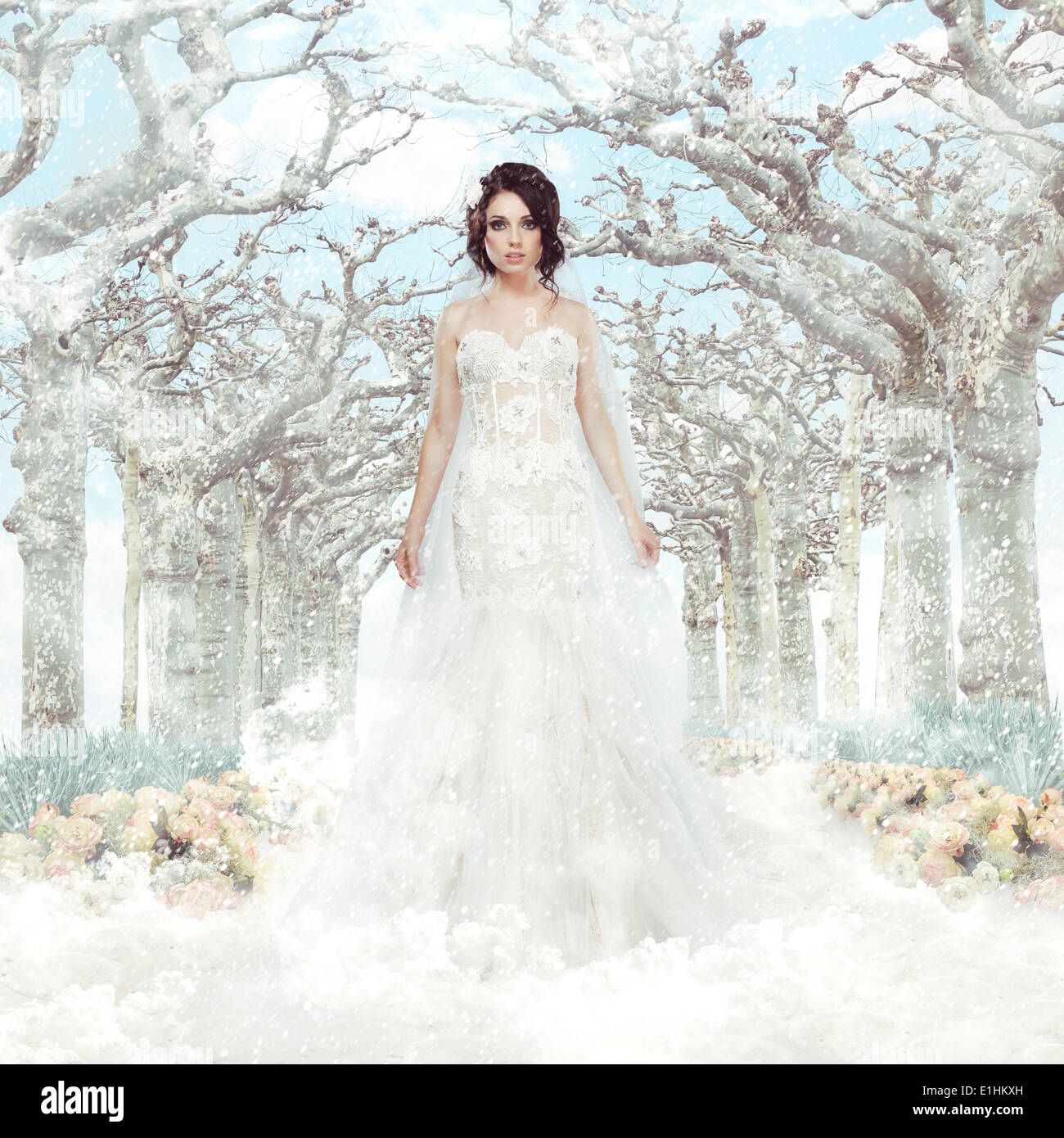 Fantasy. Matrimony. Bride in White Dress over Frozen Winter Trees and Snowflakes - Stock Image