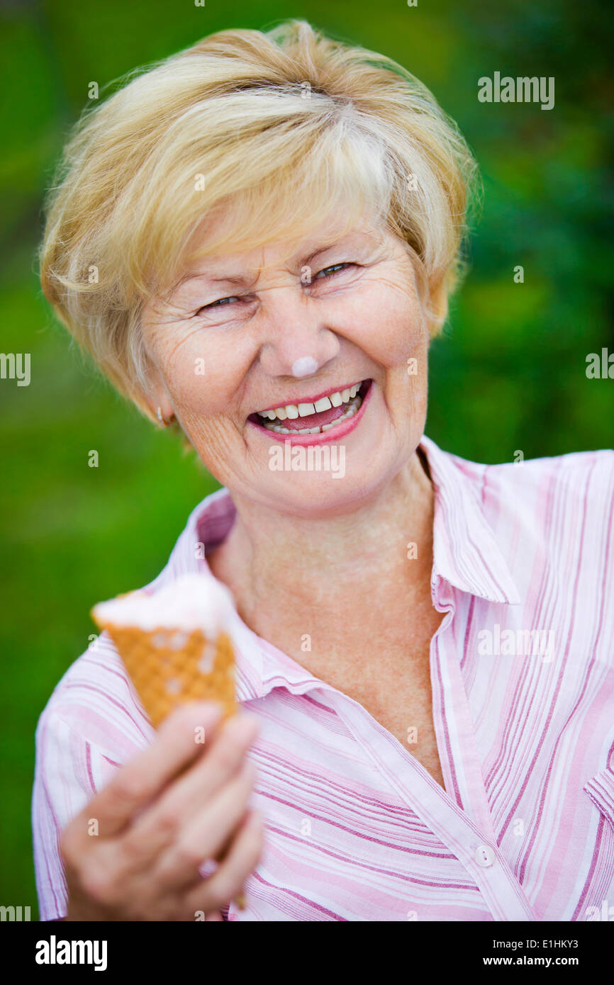 Contentment. Jubilant Ecstatic Old Woman Holding Ice-Cream and Laughing - Stock Image