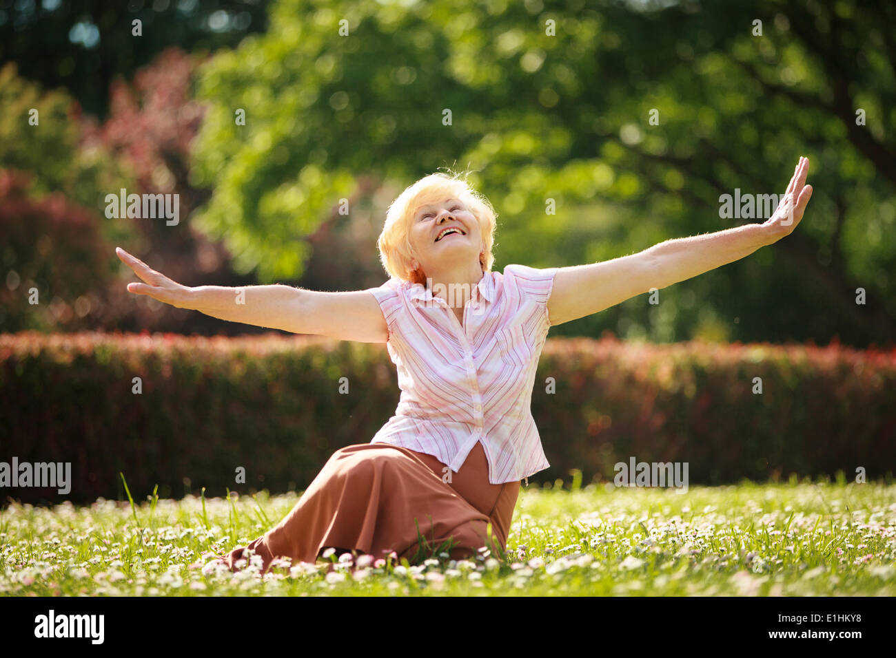 Gladness. Meditation. Mature Pleased Woman Relaxing with Outspread Arms - Stock Image