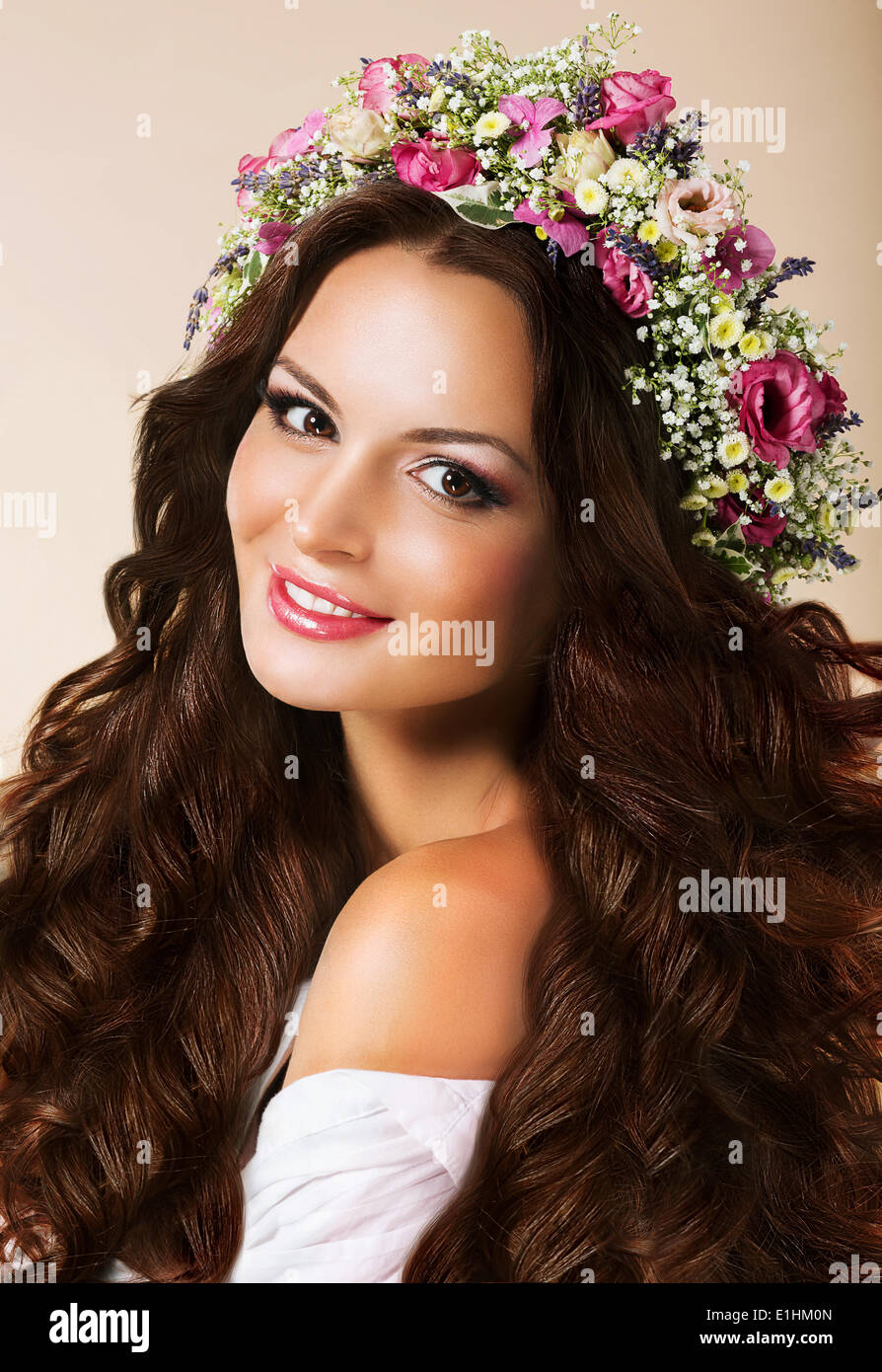 Genuine Young Woman with Flowing Healthy Hairs and Wreath of Flowers - Stock Image