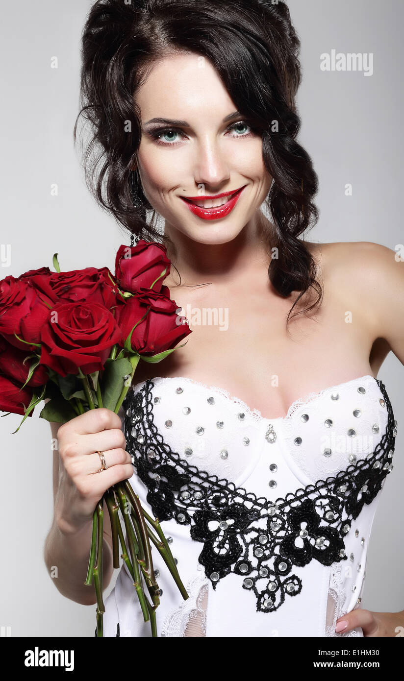 Fragrance. Beautiful Young Woman Holding Bouquet of Red Roses. Valentine's Day - Stock Image