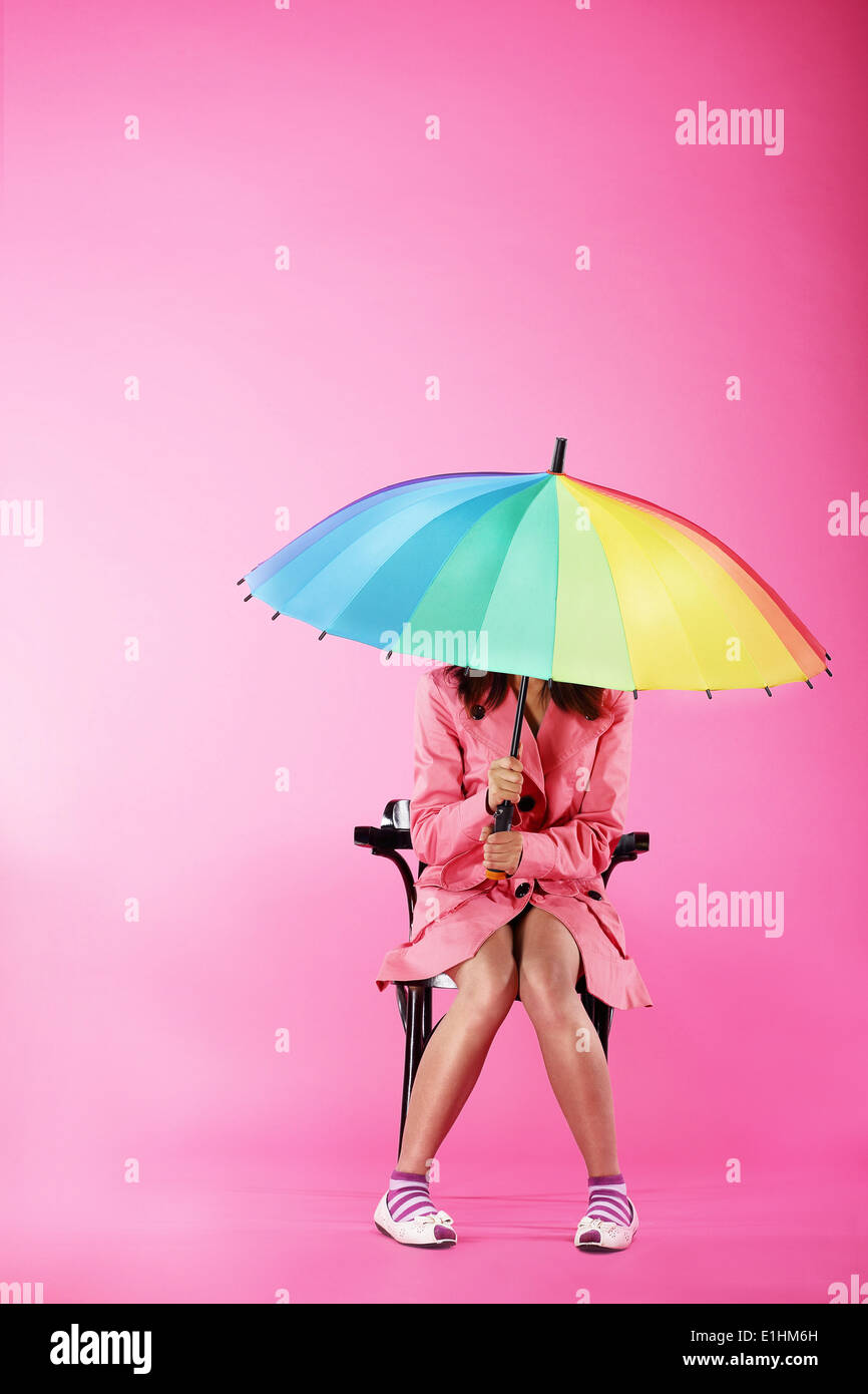 Vogue. Woman in Pink Coat sitting with Colorful Umbrella - Stock Image
