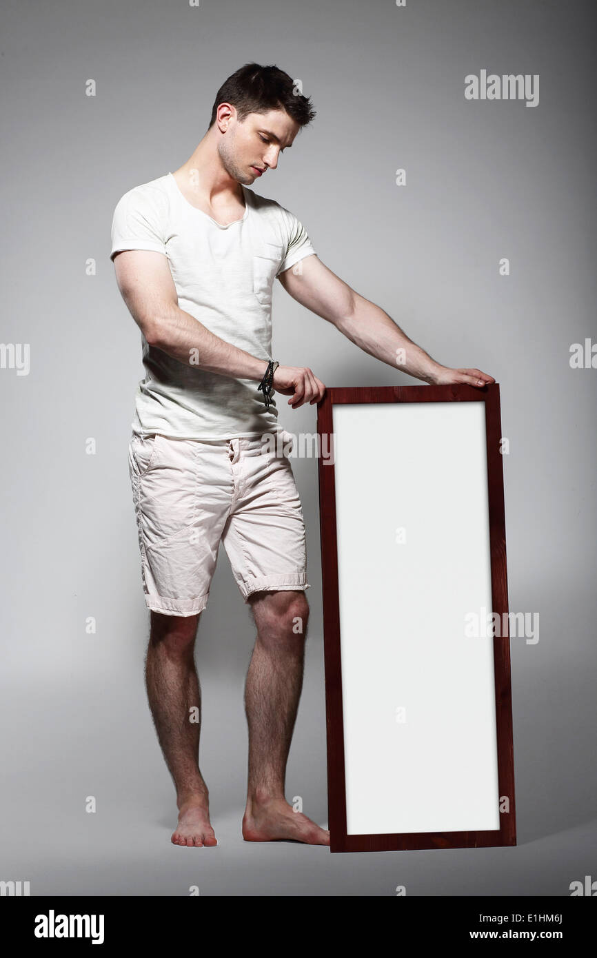 Shoeless Man Displaying White Board with Blank Space - Stock Image