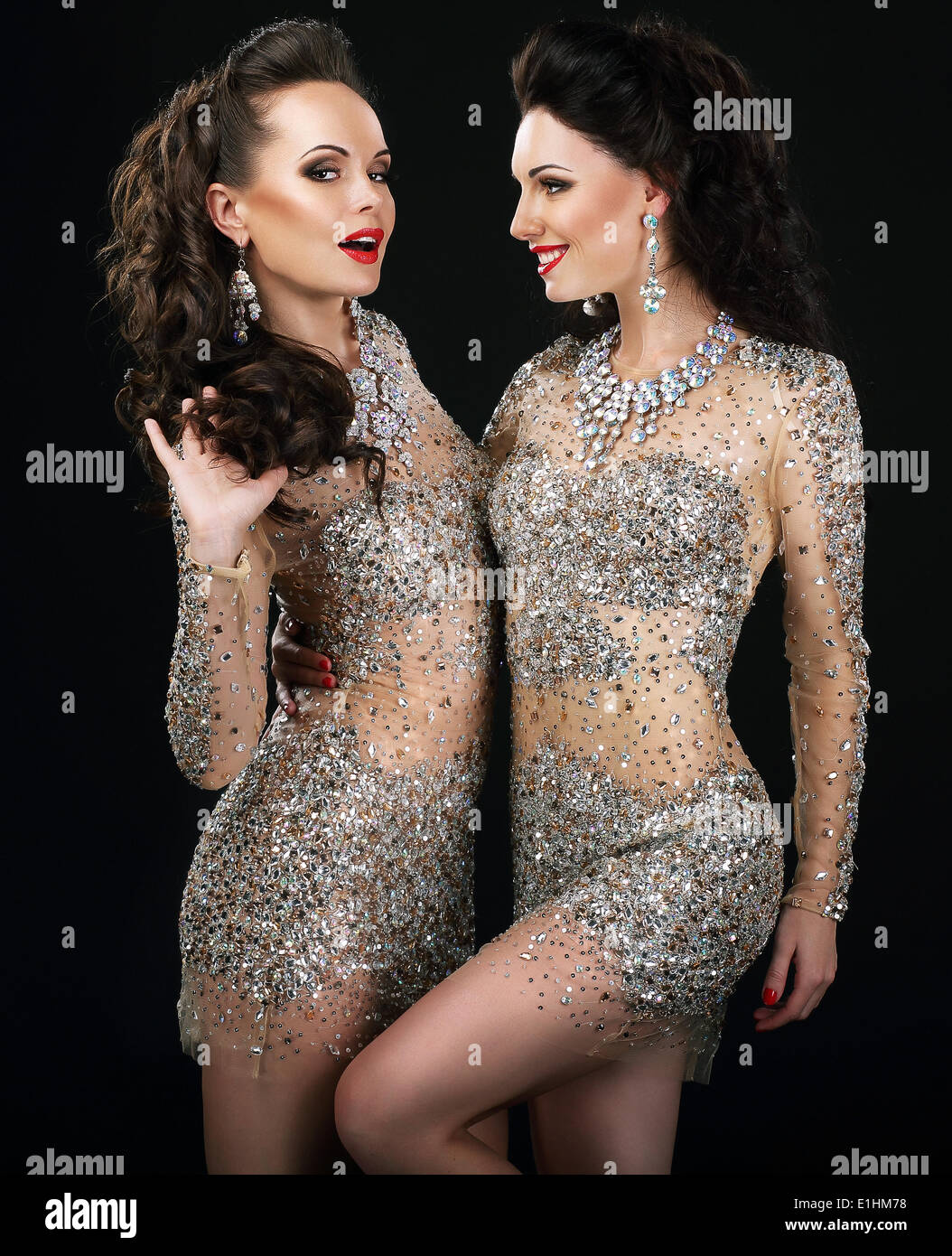 Excited Glamorous Couple in Platinum Dresses Talking - Stock Image