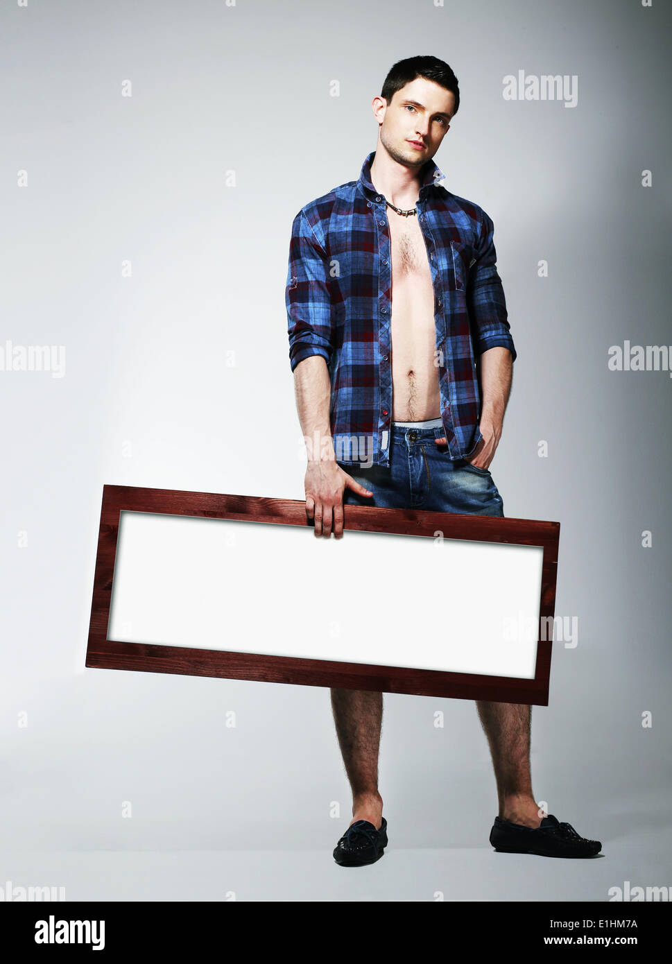 Young Man Showing Placard with White Blank Space - Stock Image