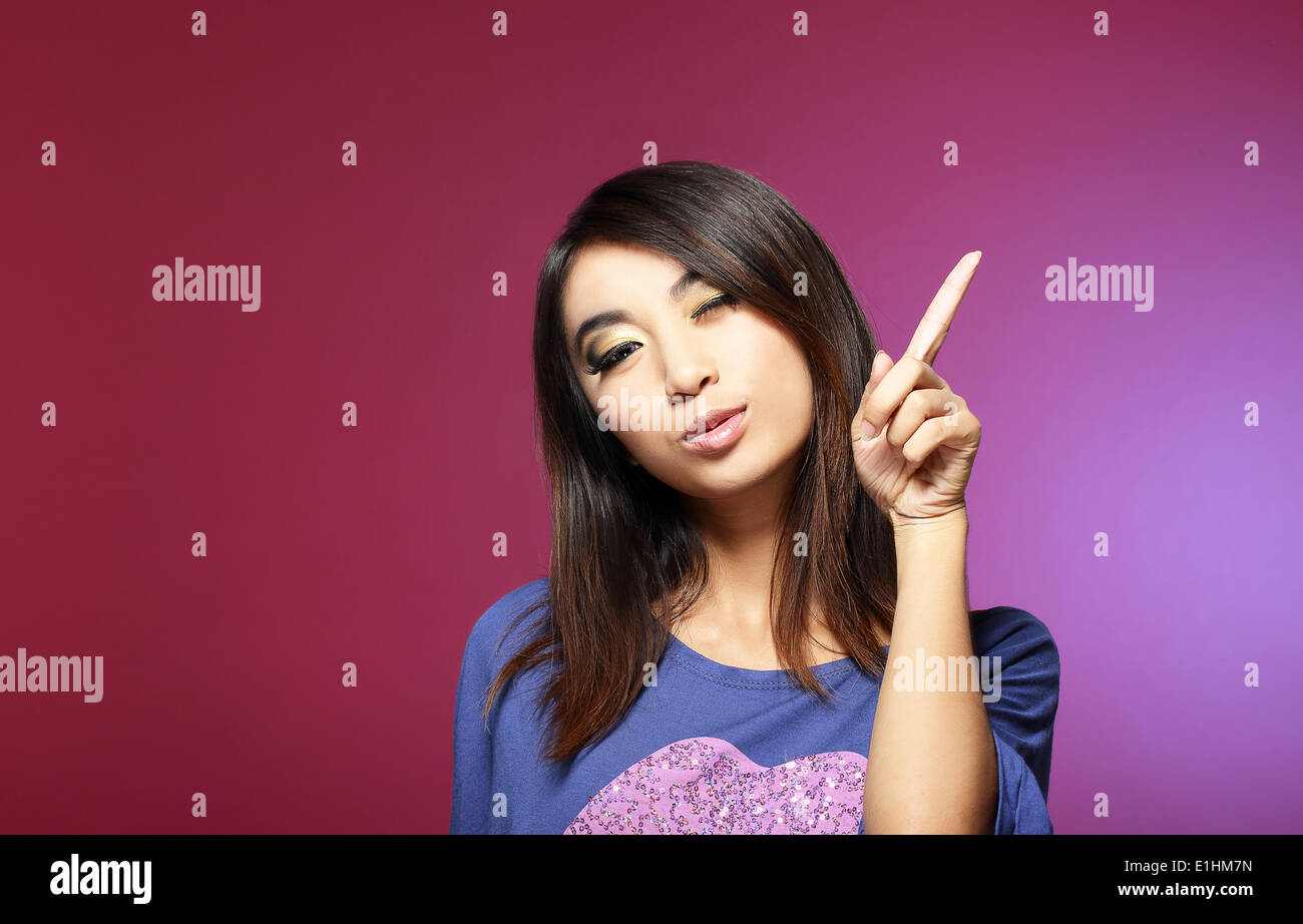 Sale Concept. Friendly Young Saleswoman Pointing with Her Index Finger Upwards - Stock Image