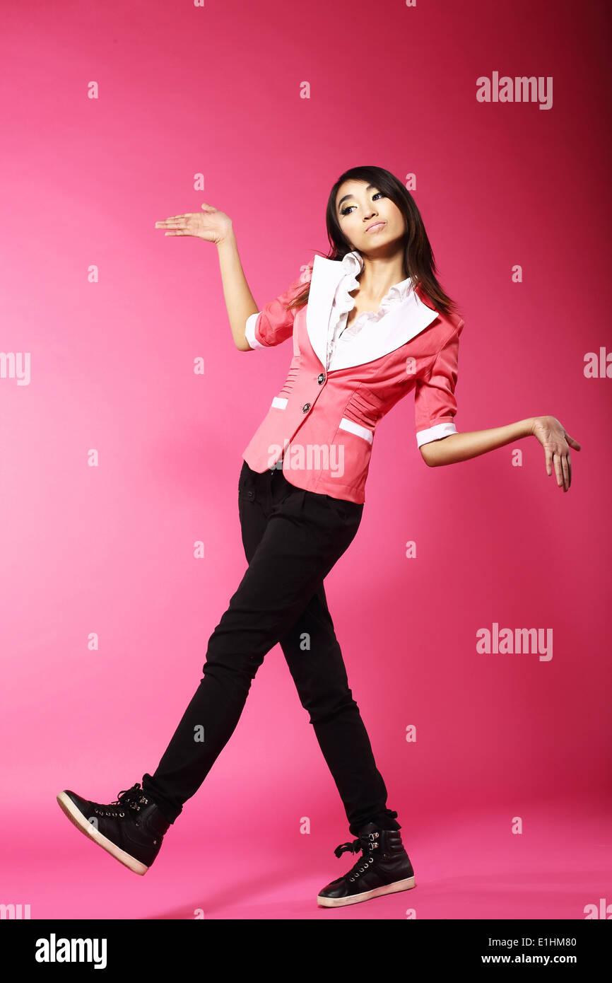 Asian Amusing Teenager Walking in Pink Studio - Stock Image