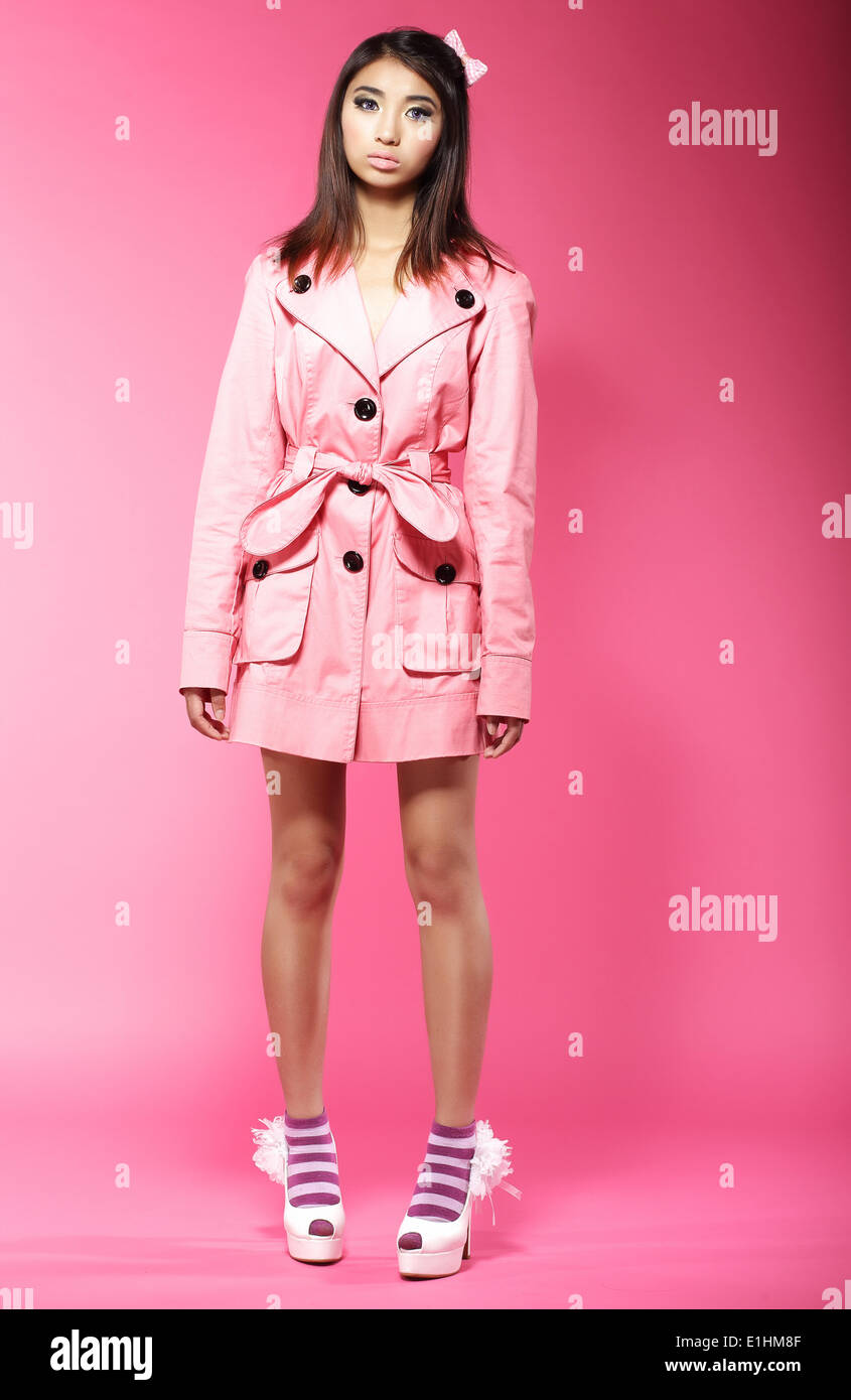 Young Asian Female Fashion Model in Pink Coat standing in Studio - Stock Image