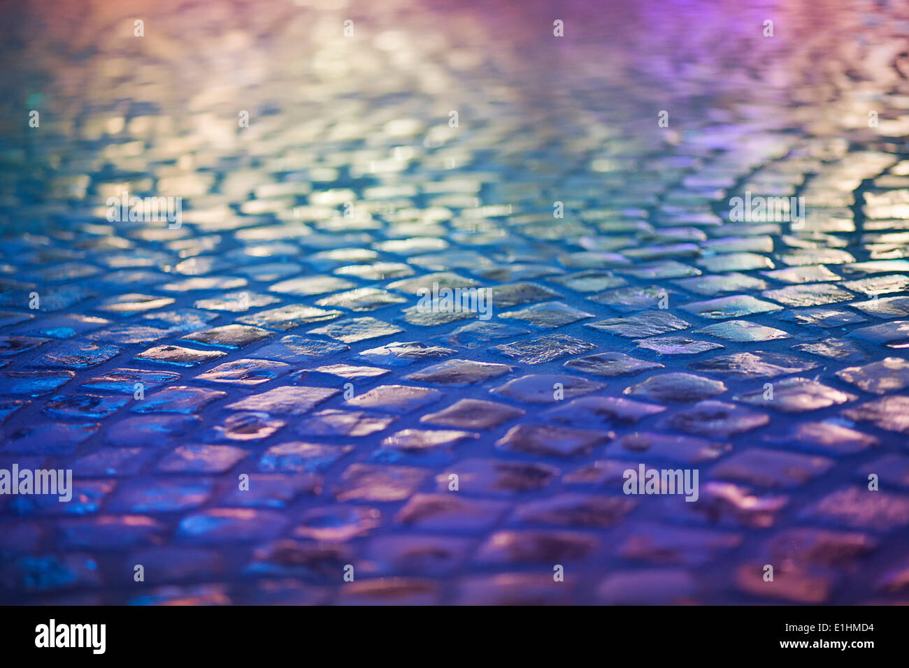 Cobble Stone Pavement - Reflexion in Urban Night. Wet Blue Sidewalk - Stock Image