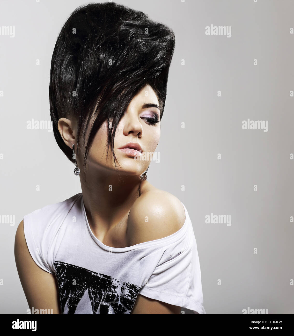 Updo Black Hair. Stylish Woman with Trendy Hairstyle with Diamond Earrings - Stock Image