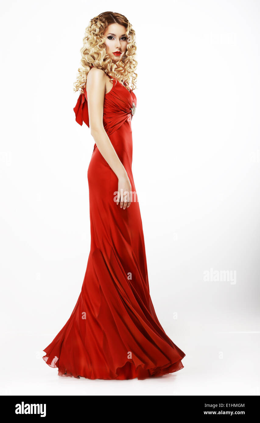 Luxury. Full Length of Elegant Lady in Red Satiny Dress. Frizzy Blond Hair - Stock Image