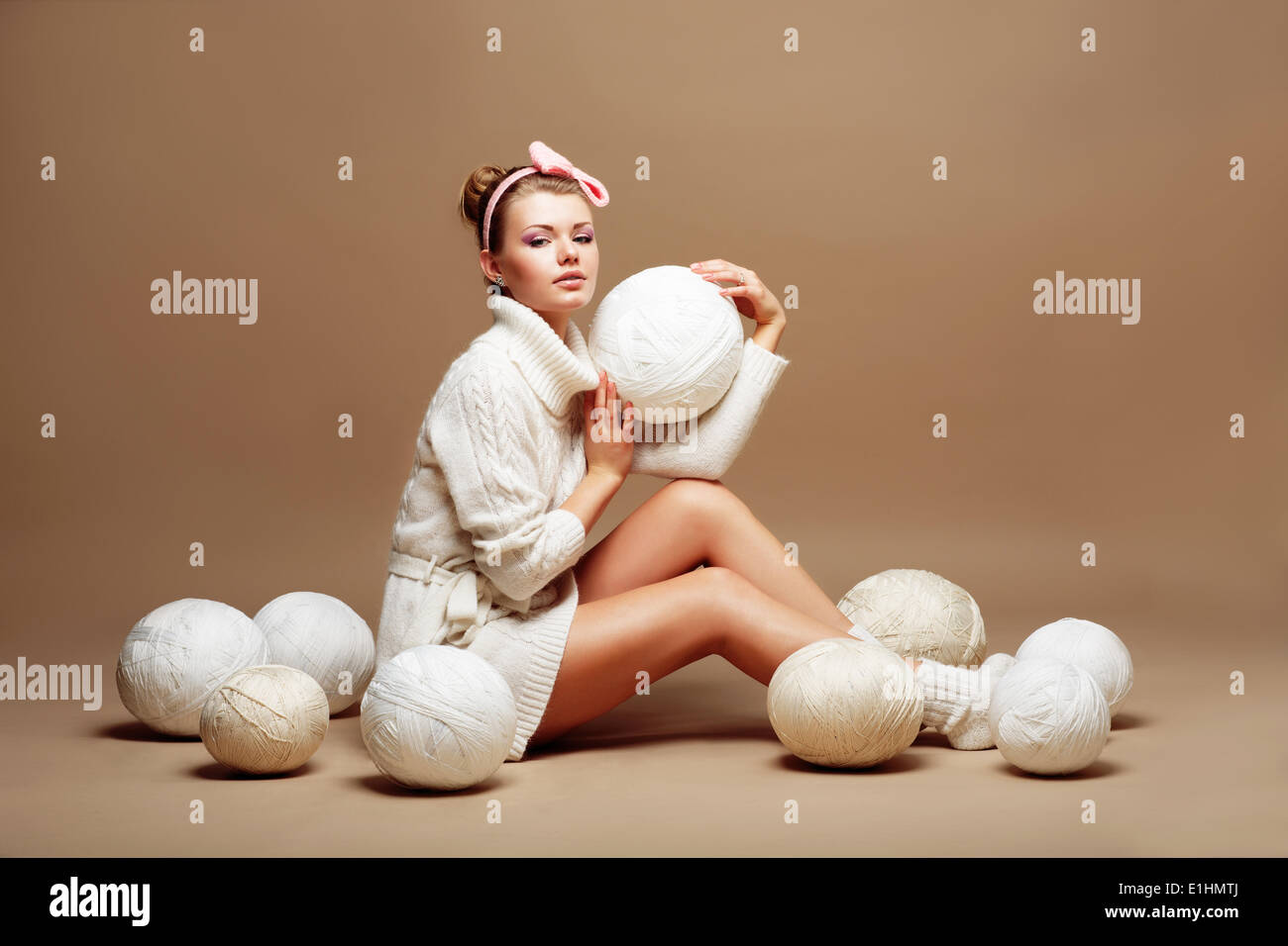 Knitting. Sewing. Woman in White Knitted Clothing with Bulk of Fluffy Clews of Yarn - Stock Image