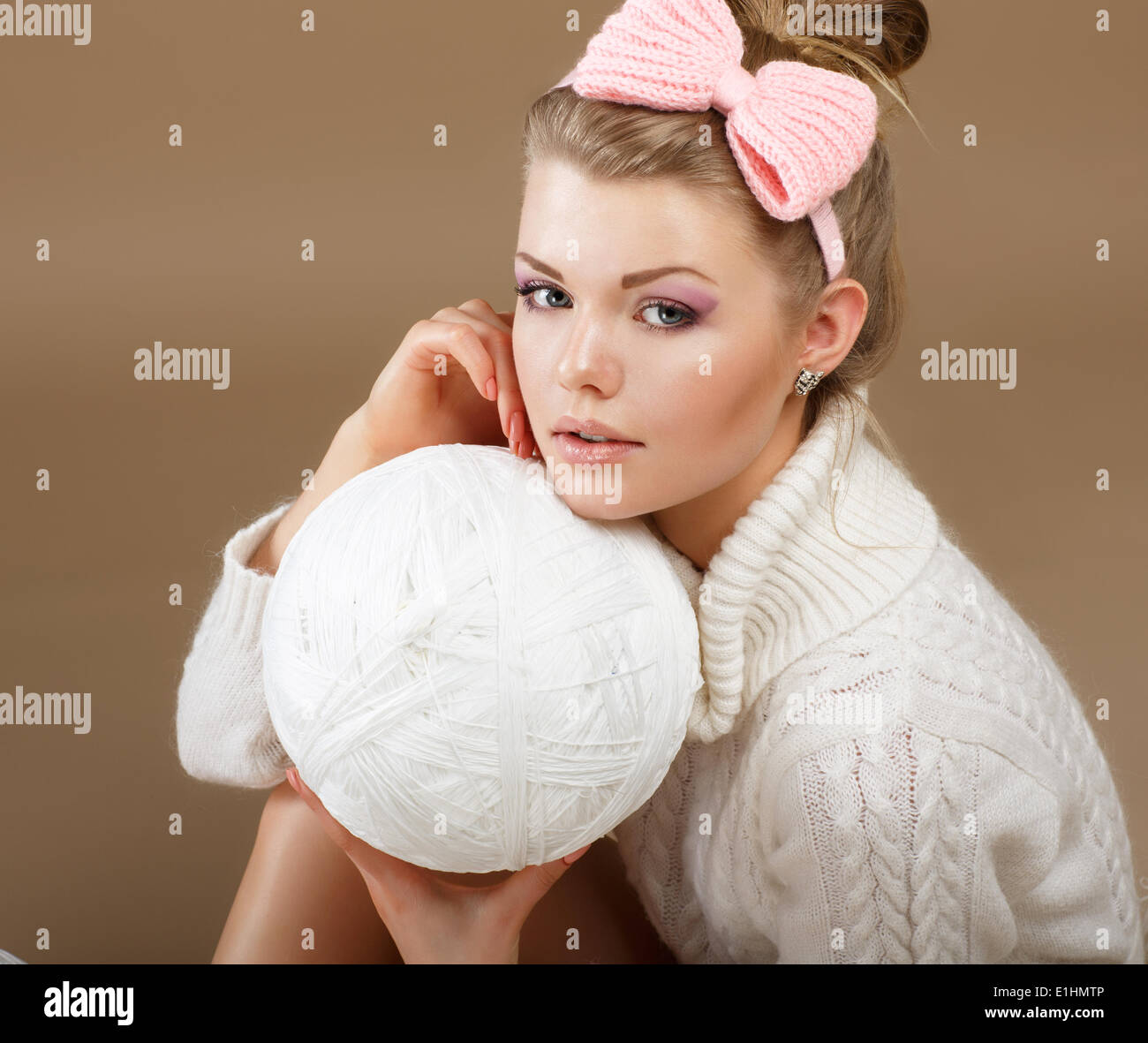 Pure Beauty. Woman in White Fluffy Knitted Pullover with Hank of Thread - Stock Image