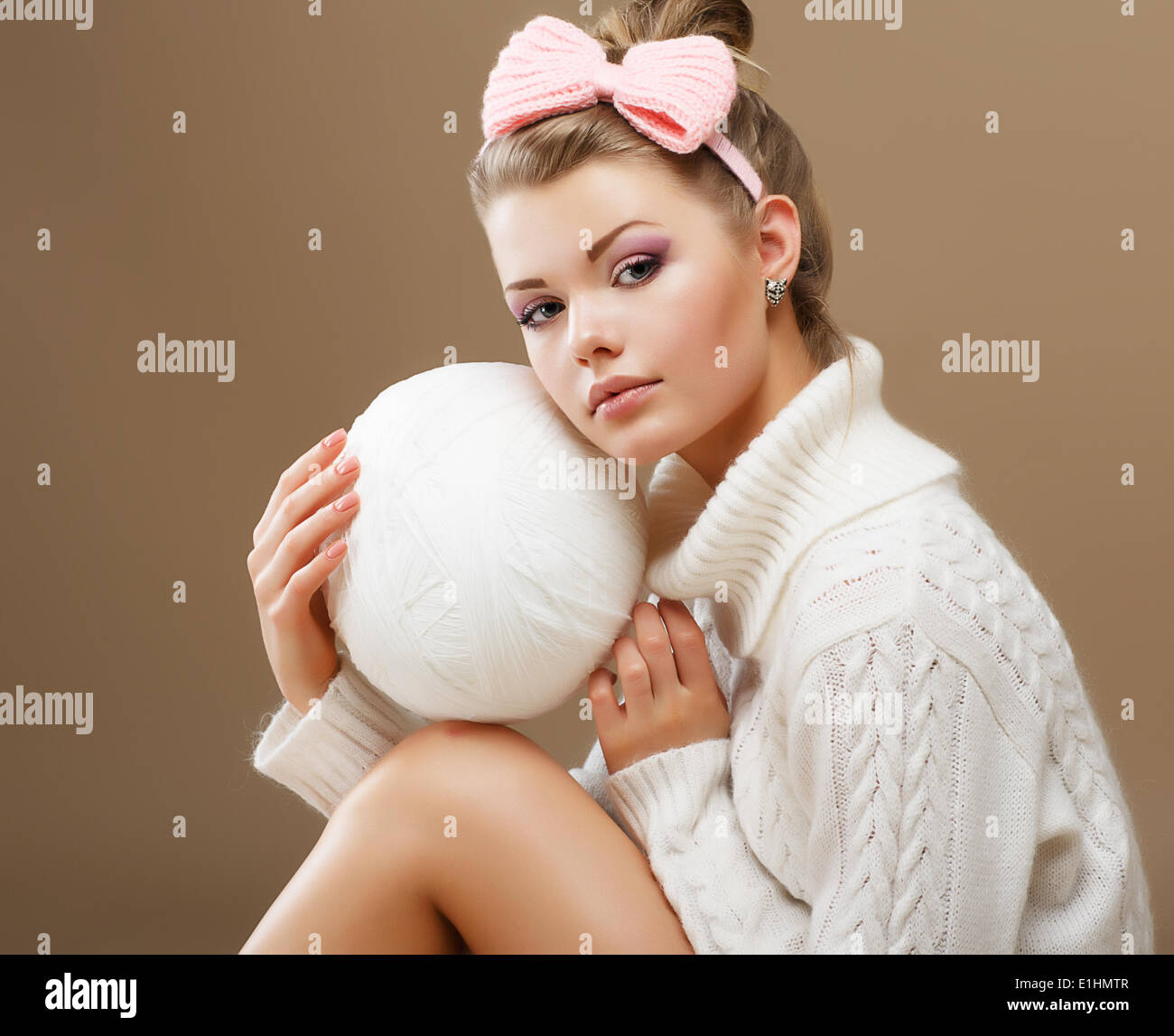 Hosiery. Beautiful Teen in Handmade Woven Sweater with White Ball of Yarn - Stock Image