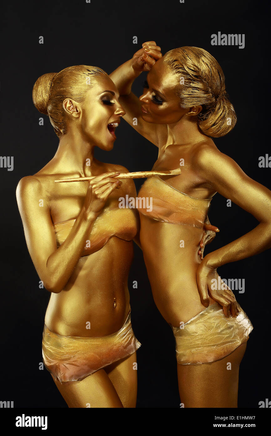 Gilt. Two Funny Women with Paintbrush. Futuristic Glossy Gold Make-up - Stock Image