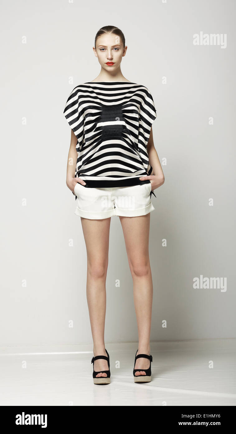Full Length of Trendy Woman in Shorts and Grey Striped Shirt. Casual Modern Collection - Stock Image
