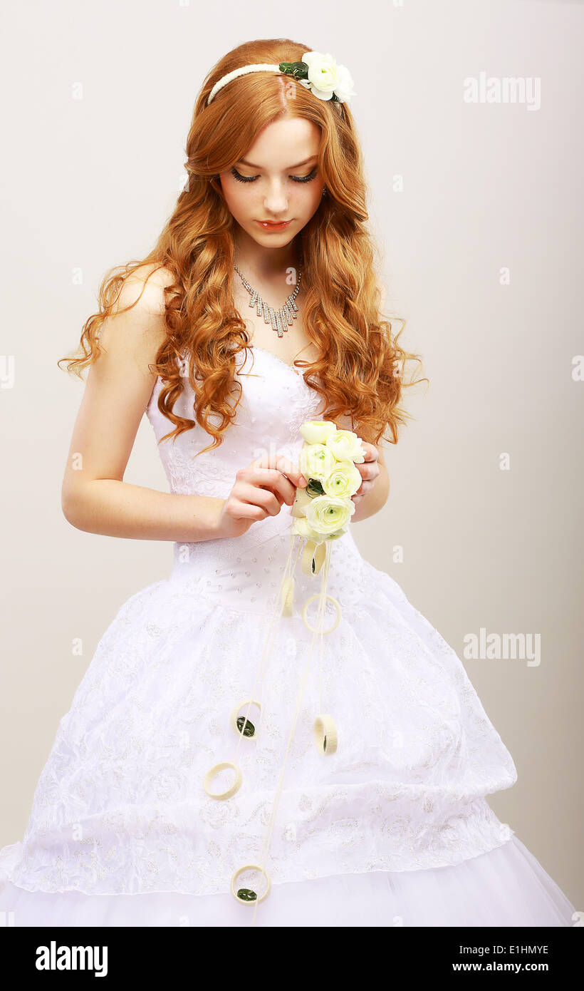 Tenderness & Romance. Red Hair Bride with Fresh Flowers in Reverie. Wedding Style - Stock Image