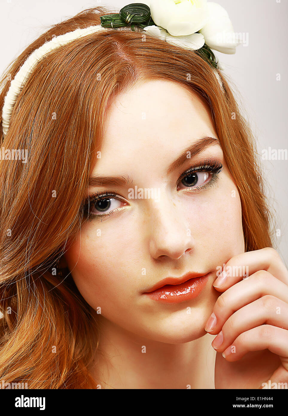 Goodness. Portrait of Young Meek Woman with White Flower on her Head - Stock Image