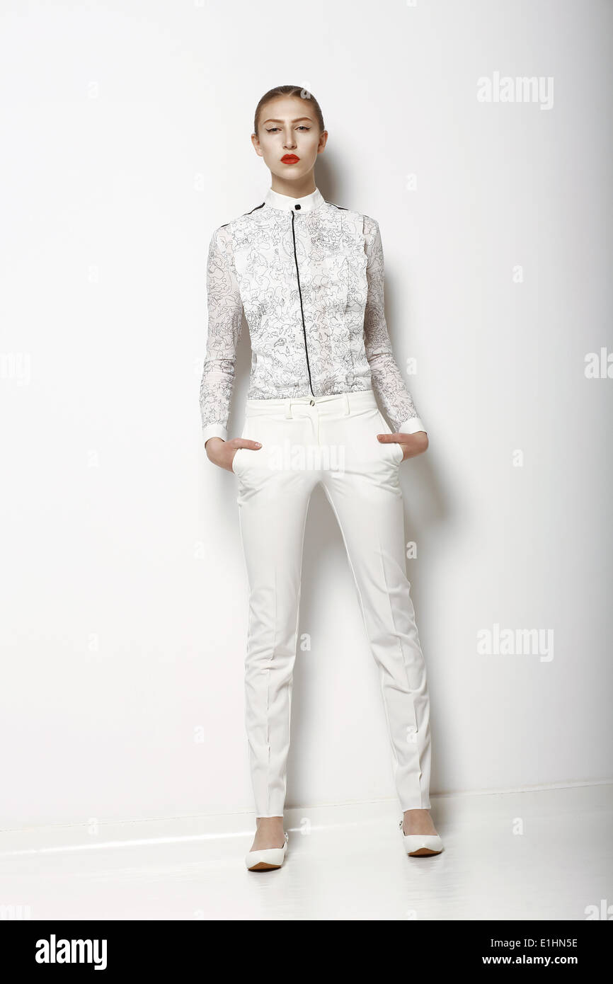 High Fashion. Trendy Woman in WHite Breeches in Graceful Pose. Spring Time Collection - Stock Image