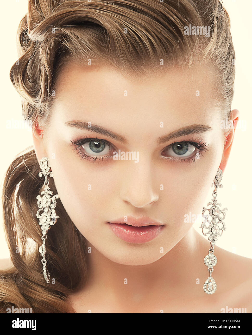 Jewelry. Portrait of Gorgeous Exquisite Woman with Shiny Earrings. Refinement - Stock Image