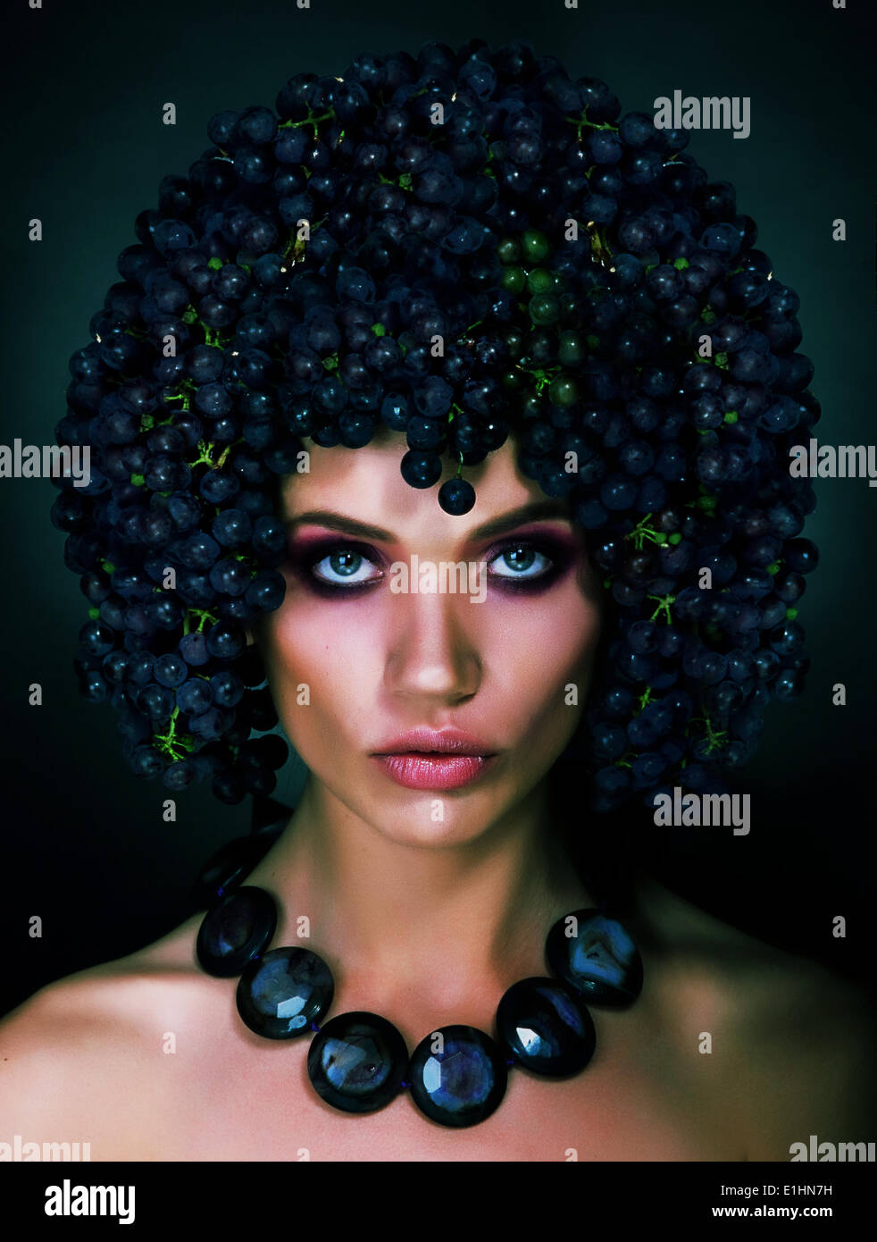 Portrait of Autumn Woman with Grapes on her Head. Trendy Hairstyle - Stock Image