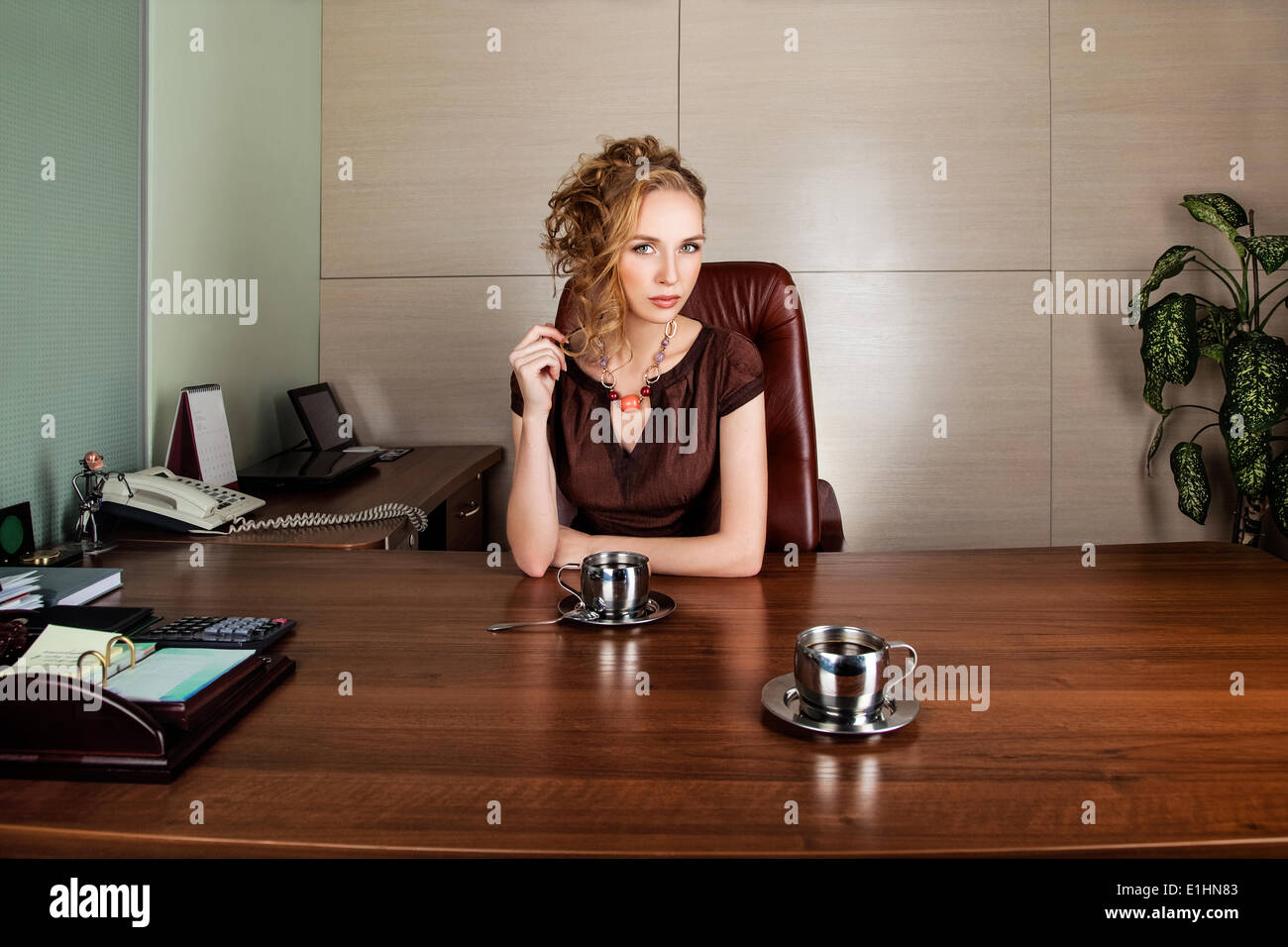 Serious businesswoman consultant in modern office interior - Stock Image