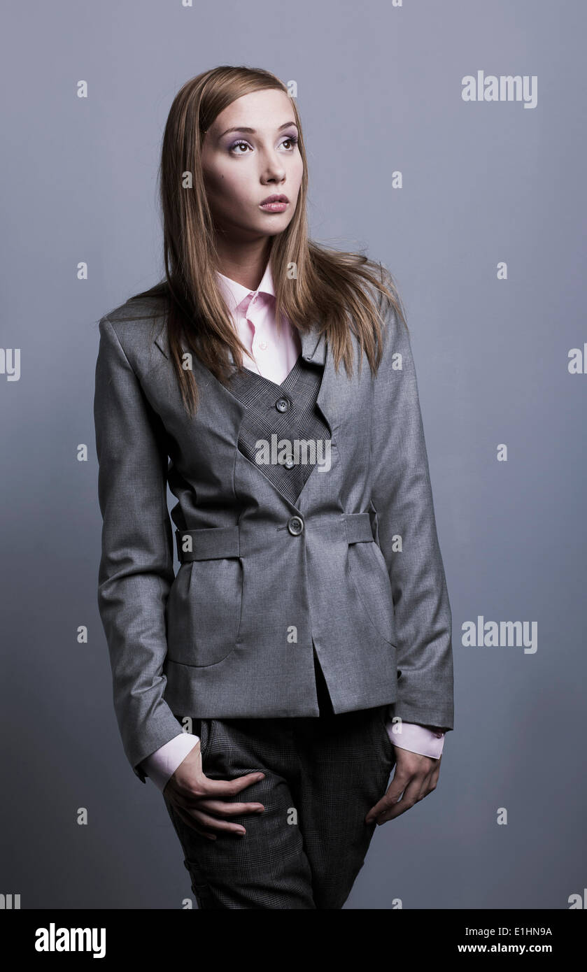 Trendy fashionable model girl posing in gray costume posing. Studio shot - Stock Image