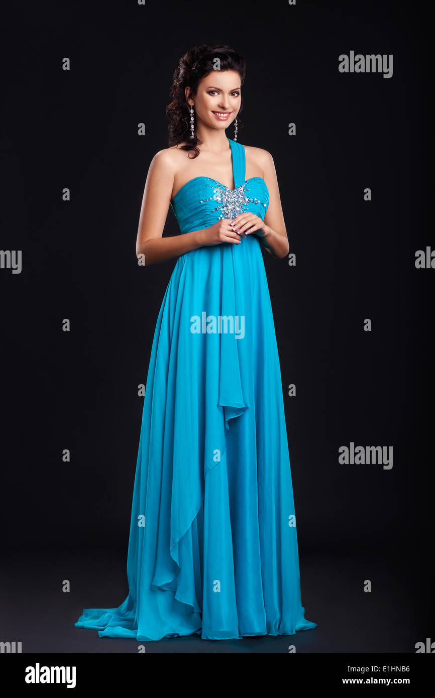 Portrait of trendy young woman in trendy blue dress smiling over black background Stock Photo