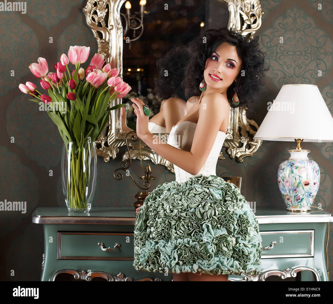 Beautiful Glamorous Woman in Retro Interior with Vase of Flowers. Reflection - Stock Image