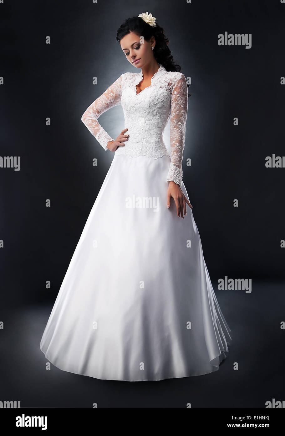 Pretty young woman in white wedding dress with flower in her head - series of photos - Stock Image