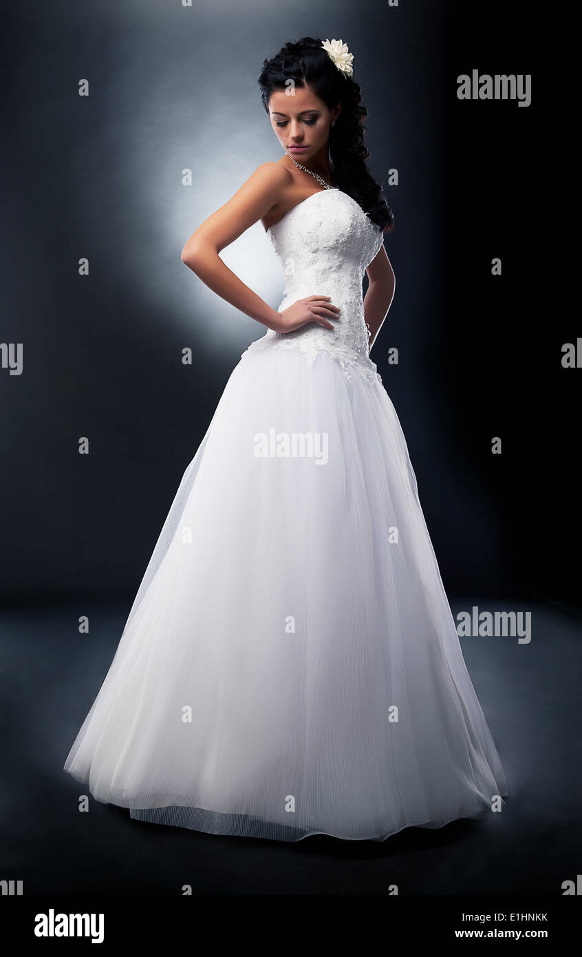 One beautiful fiancee in marital white dress posing in studio - series of photos - Stock Image